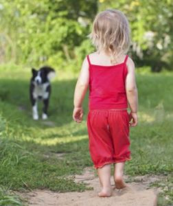photo of little child and dog in park